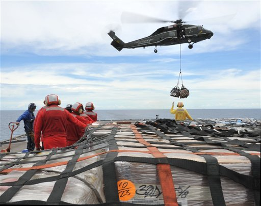In this March 12, 2011 photo provided by the U.S. Navy, sailors aboard the U.S. 7th Fleet command ship USS Blue Ridge (LCC 19) stand-by to move pallets of humanitarian relief supplies.