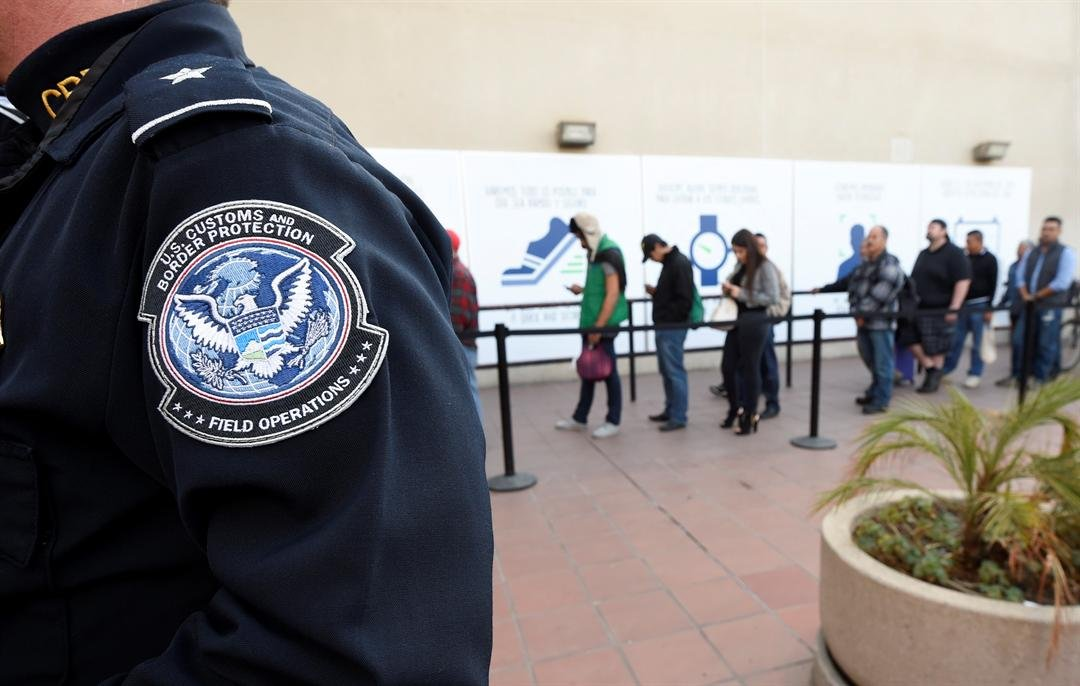 FILE - In this Dec. 10, 2015, file photo, pedestrians crossing from Mexico into the United States at the Otay Mesa Port of Entry wait in line in San Diego. (AP Photo/Denis Poroy, File)