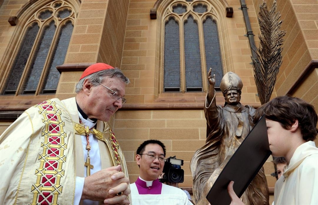 FILE - In this May 1, 2011 file photo, Cardinal George Pell, left, reads a bible during the blessing of a statue of John Paul ll at St Mary's Cathedral in Sydney, Australia. Australian police say they are charging Pell with historical sexual assault offen