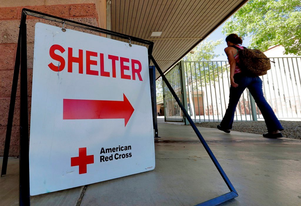 An evacuee from the Goodwin fire enters a Red Cross shelter,.