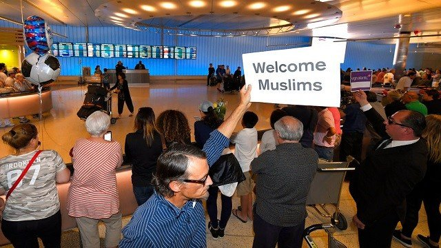 John Wider holds up a sign becoming Muslims in the Tom Bradley International Terminal at Los Angeles International Airport.