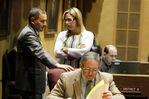 Opponents to the new Arizona immigration bills, Sen. Steve Gallardo, D-Phoenix, left, and Sen. Kyrsten Sinema, D-Phoenix, middle, talk as proponent to the new bills Sen. John McComish, R-Ahwatukee, concentrates on paperwork.