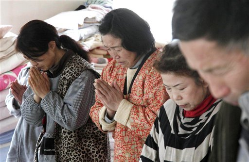 Residents observes a moment of silence for victims of the March 11 earthquake and tsunami at a shelter in Ofunato, Iwate Prefecture, at 2:46 p.m. on Friday, March 18, 2011 at the time when a strong earthquake hit northeastern Japan one week ago.
