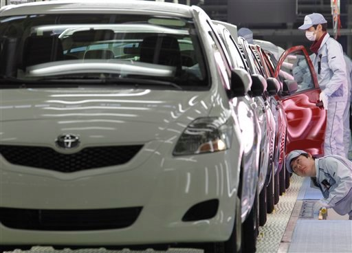 FILE - In this file photo taken Feb. 16, 2011, workers give the final check on Yaris compact sedans, set for export to North America, on a newly opened assembly line at a plant of Toyota Motor Co.'s group company Central Motor Co. in Ohira in Miyagi Prefe