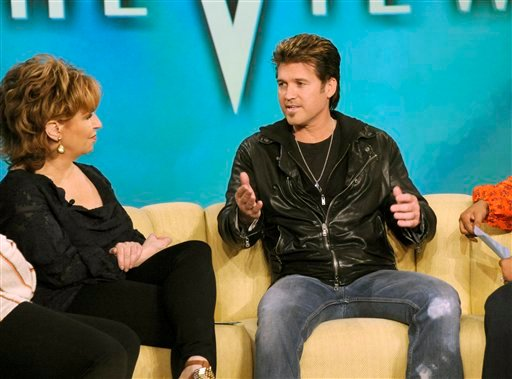 """In this March 17, 2011 publicity image released by ABC, actor and country singer Billy Ray Cyrus is shown with Joy Behar, during an interview for """"The View"""" in New York."""