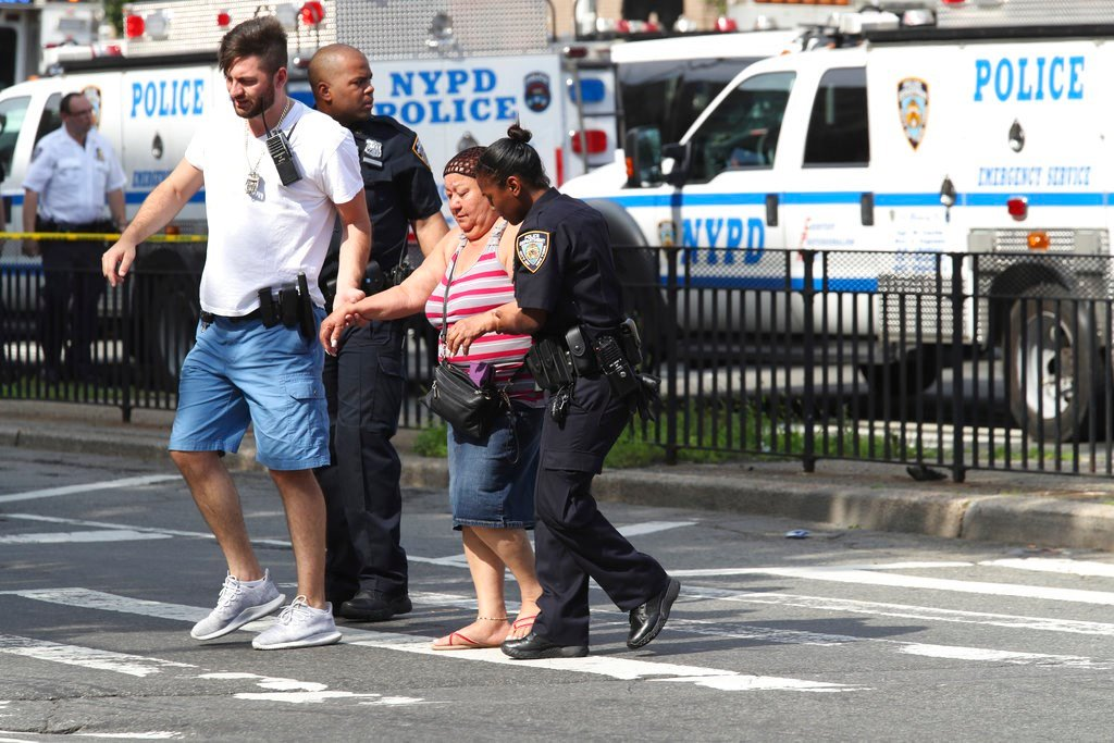 Police help people cross the street outside the Bronx Lebanon Hospital in New York after a gunman opened fire there on Friday, June 30, 2017.