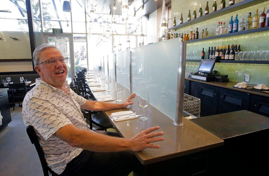 "Joel LaSalle, Current Fish and Oyster owner, sits in front of a partition known as a ""Zion Curtain"" that prevents customers from seeing their alcoholic drinks being mixed and poured, before it's taken down at his restaurant"