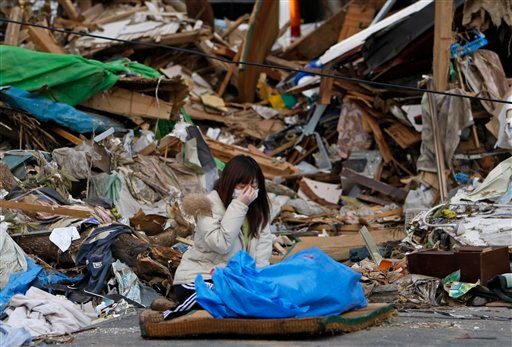 Tayo Kitamura, 40, kneels in the street to caress and talk to the wrapped body of her mother Kuniko Kitamura, 69, after Japanese firemen discovered the dead woman inside the ruins of her home in Onagawa, northeastern Japan, Saturday, March 19, 2011.