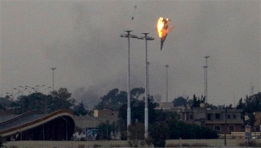 A warplane is seen being shot down with the pilot parachuting out of it over the outskirts of Benghazi, eastern Libya, Saturday, March 19, 2011.