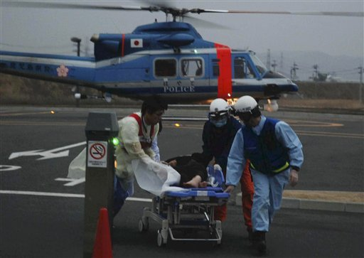 A woman on a stretcher gets carried into the Ishinomaki Red Cross Hospital in Ishinomaki, northern Japan, Sunday, March 20, 2011, after the March 11 earthquake and tsunami. (AP Photo/The Yomiuri Shimbun, Masanori Yamashita)