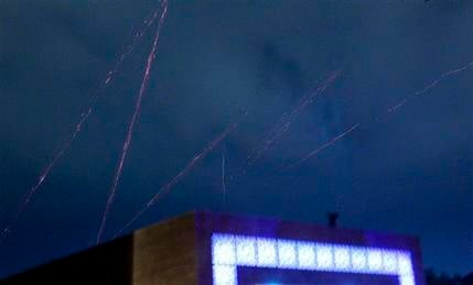 Tracer bullets are fired in the skies over Tripoli, Libya, as heavy explosions rock the city early Sunday, March 20, 2011. (AP Photo/Jerome Delay)