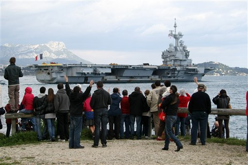 People wave to relatives aboard the French nuclear-powered aircraft carrier Charles de Gaulle at Toulon military harbor, southern France, Sunday, March 20, 2011, as he leaves its home to off Lybian coasts. (AP Photo/Claude Paris)