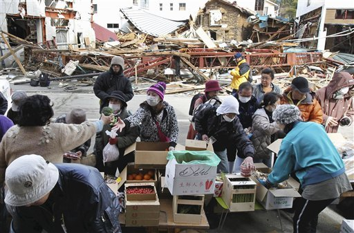 People shop for produce at a makeshift store at a devastated area in Kesennuma, northern Japan, Sunday, March 20, 2011, after last week's earthquake and tsunami. (AP Photo/The Yomiuri Shimbun, Kaname Muto)