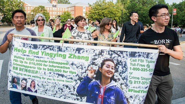 Yingying Zhang's father Ronggao Zhang, left, and her friend Xiaolin Hou carry the banner as community members join together to walk for Yingying.