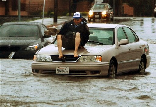 A man gets ready to jump off the hood of his car, stalled on flooded Vineland Ave between Vanowen and Sherman Way, in the North Hollywood area of Los Angeles March 20, 2011. (AP Photo/Mike Meadows)