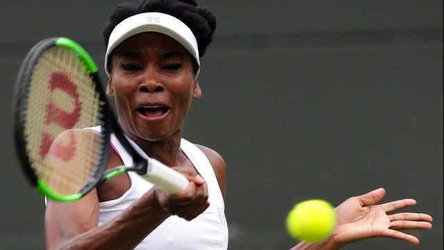Venus Williams of the United States returns to Belgium's Elise Mertens during their Women's Singles Match on the opening day at the Wimbledon.