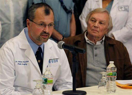 Plastic surgeon Dr. Bohdan Pomahac, left, speaks during a news conference at Brigham and Women's Hospital in Boston March 21, 2011 as Del Peterson, grandfather of face transplant recipient Dallas Wiens, listens at right. (AP Photo/Elise Amendola)
