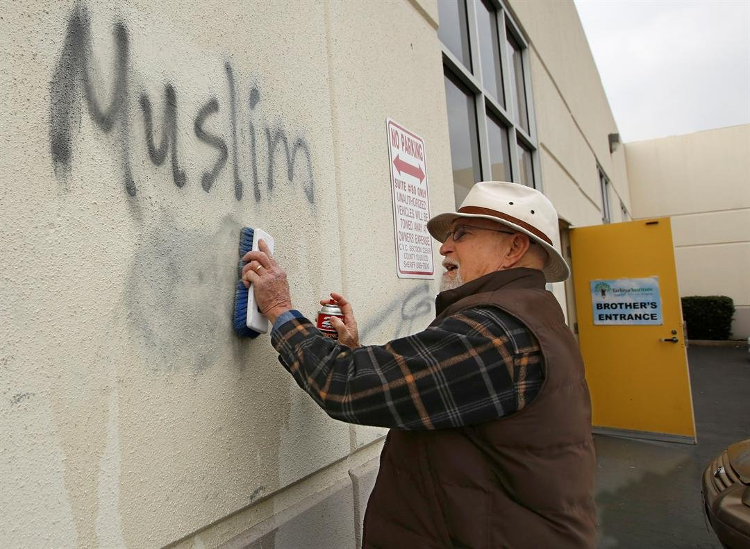 FILE - In this Feb. 1, 2017 file photo, Tom Garing cleans up racist graffiti painted on the side of a mosque in what officials are calling an apparent hate crime in Roseville, Calif. The report released Monday, July 3, 2017, shows 931 hate crimes statewid