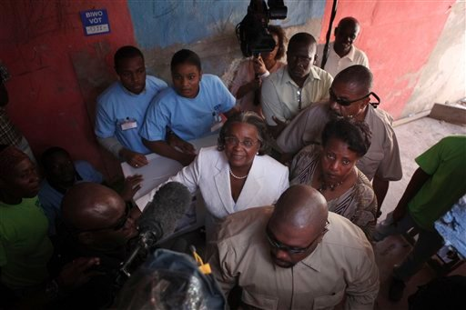Presidential candidate Mirlande Manigat, center, looks on as she arrives to cast her ballot at a polling station in Port-au-Prince, Haiti, Sunday, March 20, 2011.