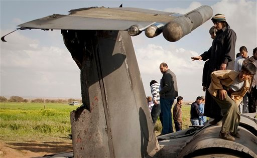 Libyans inspect the wreckage of a US F15 fighter jet after it crashed in an open field in the village of Bu Mariem, east of Benghazi, eastern Libya, Tuesday, March 22, 2011, with both crew ejecting safely.