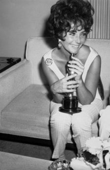 FILE - In this April 19, 1961 file photo, actress Elizabeth Taylor holds the Oscar she won as 1960's best film actress for her role in 'Butterfield 8,' while speaking with reporters in Hollywood, Calif.