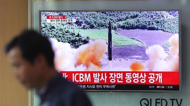 A man walks by a TV screen showing a local news program reporting about North Korea's missile firing at Seoul Train Station in Seoul, South Korea, Wednesday, July 5, 2017.