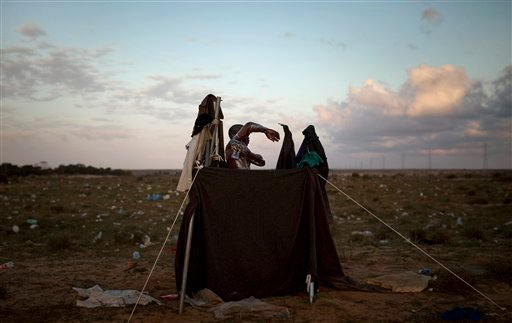 A man from Sudan, who used to work in Libya and fled the unrest in the country, takes a shower in a improvised makeshift shower after crossing from Libya near the Tunisia-Libyan border March 23, 2011. (AP Photo/Emilio Morenatti)