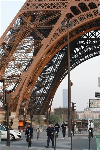 Police officers take position at the foot of the Eiffel Tower following a bomb threat in Paris, Wednesday March 23, 2011. A suspicious package and phoned-in bomb threat prompted the Eiffel Tower to evacuate nearly 4,000 tourists from the Paris landmark.
