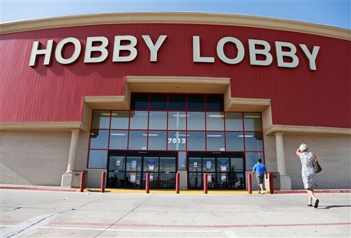 FILE - In this Monday, June 30, 2014, file photo, customers walk to a Hobby Lobby store in Oklahoma City.  (AP Photo/Sue Ogrocki, File)