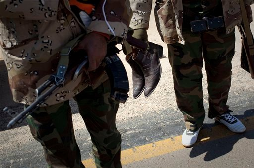 A libyan rebel carries his boots after he was supplied with sneakers on a checkpoint on the frontline near Zwitina, the outskirts of the city of Ajdabiya, south of Benghazi, eastern Libya, Thursday, March 24, 2011. (AP Photo/Anja Niedringhaus)
