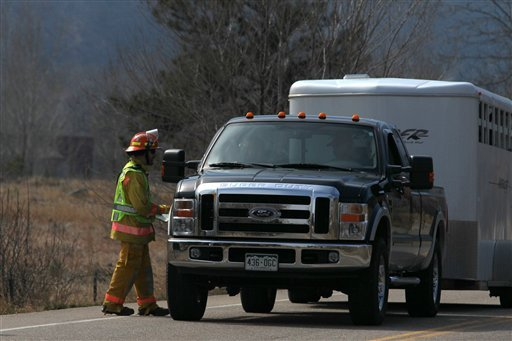 A firefighter gets resident information from a homeowner evacuating animals from the Left Hand Canyon area north of Boulder, Colo. Friday, March 11, 2011.
