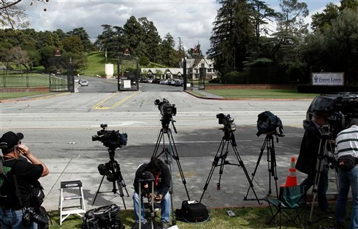 Media wait for a caravan of limousines containing the family of Elizabeth Taylor to leave the Forest Lawn memorial park and mortuary in Glendale, Calif. on Thursday, March 24, 2011. Taylor, 79, passed away Wednesday in Los Angeles. (AP Photo/Matt Sayles)