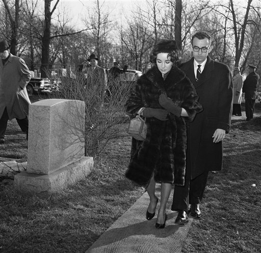 FILE - In this March 2, 1959 file photo, actress Elizabeth Taylor, accompanied by her physician, Dr. Rexford Kennamer, walks through Waldheim Cemetery in Chicago where she attended ceremony dedicating the grave marker of her late husband.