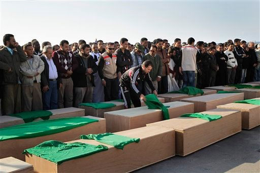 Men gather at a mass funeral for people killed in Coalition bombings, officials said, in Tripoli, Libya, Thursday March 24, 2011.