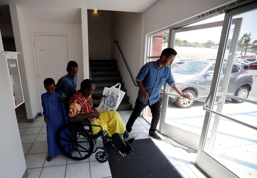 Ali Said, of Somalia, center, leaves a center for refugees with his two sons, as refugee caseworker Mohamed Yassin, right, holds open the door Thursday, July 6, 2017, in San Diego.