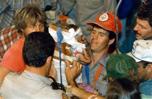 In this October 1987 file photo, rescue workers carry 18-month-old Jessica McClure to safety in Midland, Texas after she was trapped for 58 hours after she plunged 22 feet into an abandoned water well. (AP Photo/Eric Gay, File)