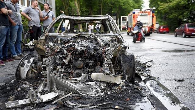 People look at a burnt-out car in Hamburg, Germany, early Friday, July 7, 2017, after protests against the G-20 summit. The leaders of the group of 20 meet Friday and Saturday in Hamburg. (Axel Heimken/dpa via AP)