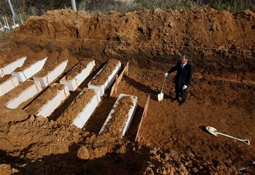 A Japanese funeral company worker looks at the coffins before burying during a mass funeral in Yamamoto, northeastern Japan Saturday, March 26, 2011. (AP Photo/Shuji Kajiyama)