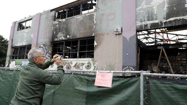 A man takes cell phone photos at the scene of a warehouse fire in Oakland , Calif.