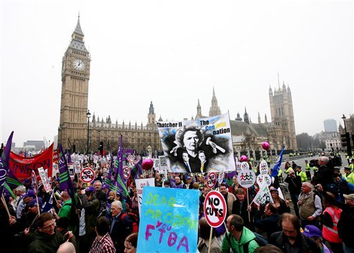 Demonstrators march past Parliament Square in London to protest against Government spending cuts Saturday March 26, 2011. (AP)