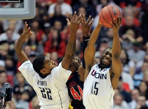 Connecticut's Roscoe Smith, left, goes and Kemba Walker, right, battle for a rebound with Arizona's Solomon Hill, center, during the first half of a West regional final in the NCAA college basketball tournament (AP)