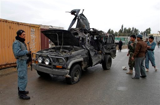In this Saturday, Jan. 29, 2011 file photo, an Afghan policeman stands near a vehicle which carried the deputy governor of Kandahar. (AP)