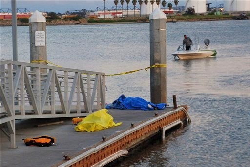 Bodies are seen covered on a dock in San Diego, Calif. Sunday, March 27, 2011, after a sailboat with nine people aboard capsized and sank in the San Diego Bay, leaving two men drowned and seven people injured, authorities said. (AP Photo/Jim Grant)