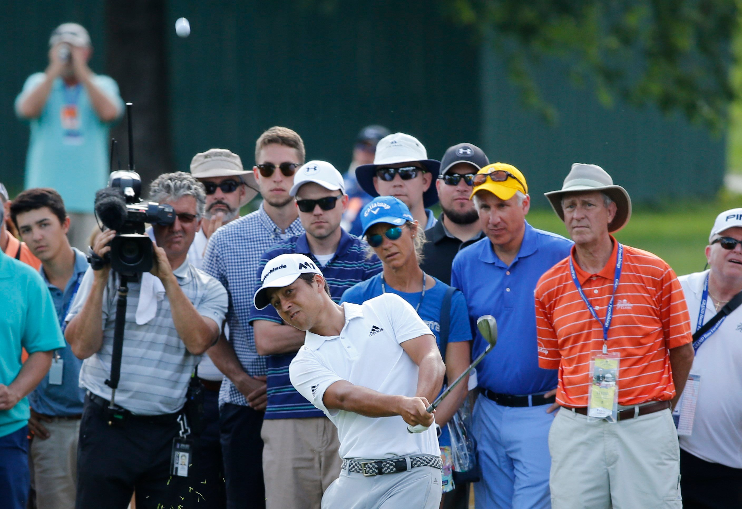 Xander Schauffele, center, hits up to the 17th green during the Greenbrier Classic PGA Tour golf tournament Sunday, July 9, 2017, in White Sulphur Springs, W.Va. (AP Photo/Steve Helber)
