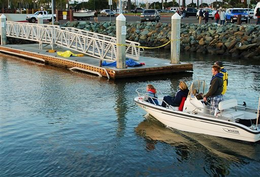 A boat approaches a dock where two bodies lie covered in San Diego, Calif. Sunday, March 27, 2011, after a sailboat with nine people aboard capsized and sank in the San Diego Bay, leaving two men drowned and seven people injured, authorities said. (AP)