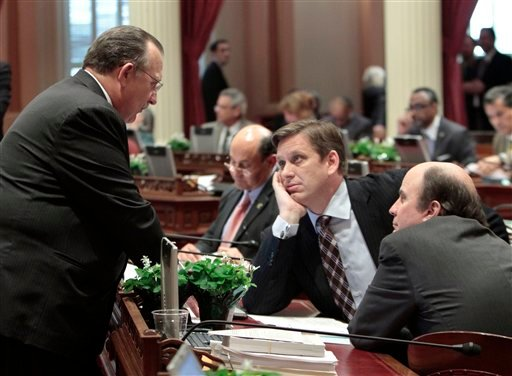 State Senate Minority Leader Bob Dutton, R-Rancho Cucamonga, left, talks with GOP lawmakers, Sen. Tony Strickland, R-Thousand Oaks, center, and Mark Wyland, R-Solana Beach during the debate over Gov. Jerry Brown's state budget plan at the Capitol.