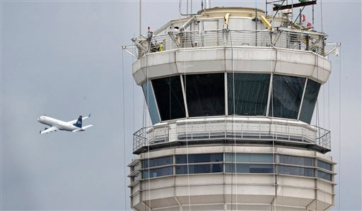 A passenger jet flies past the FAA control tower at Washington's Ronald Reagan National Airport, Thursday, March 24, 2011.