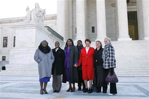 Betty Dukes, left, stands with other plaintiffs and their families outside of the Supreme Court in Washington, Tuesday, March 29, 2011, prior to attending a case of women employees against Wal-Mart.