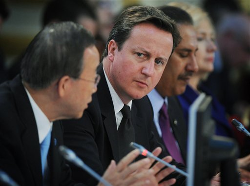 British Prime Minister David Cameron, centre, listens to UN Secretary General Ban Ki-Moon, left, speak at the opening of the Libya Conference in London Tuesday March 29, 2011.