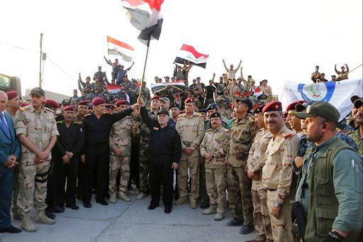 Iraq's prime minister Haider al-Abadi raises the national flag as he addresses forces from a small base on the edge of Mosul's Old City. (Iraqi Prime Minister's Media Office via AP)